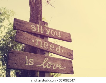All you need is love - inspirational quote on natural  wooden plate. : Vintage style and filtered process.