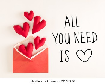 All You Need Is Love message with red heart cushions coming out of an envelope