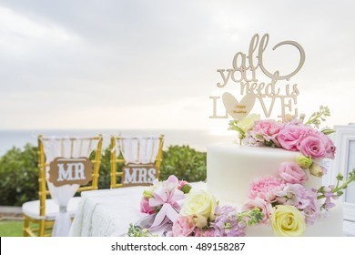 All you need is love put on wedding cake. Background is chair for Mr. groom and Mrs. bride, wedding at Phuket, Thailand