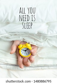 All you need is sleep. alarm clock in hand among blankets. Hand holding alarm clock in bed. concept of laziness, sleep, world sleep day, time to get up.