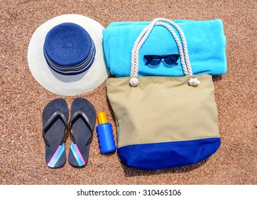 All you need for a summer vacation at the beach with a sunhat, flip flops, towel, sunglasses, sunscreen and beach bag neatly laid out on a sandy tropical beach, overhead view
