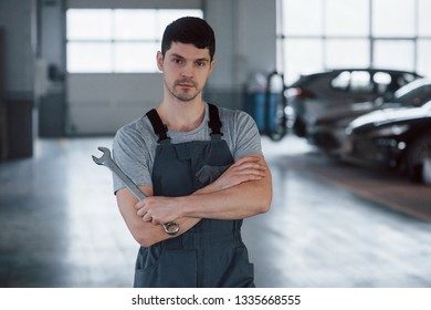 All for your vehicle. Portrait of serious worker in uniform that stands in his workshop with wrench in hand.