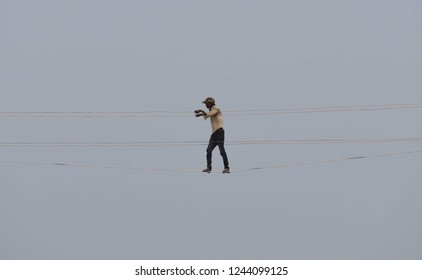 Allahabad: An electricty board worker walks on wire during install a temporary line for the upcoming Kumbh at Sangam in Allahabad on 29-11-2018.