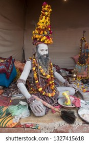 Allahabad / India 3 February 2019 A Naga-baba sits in his tent wearing a crown of rudraksh beads with Garlands at the Kumbha Mela in Allahabad Uttar Pradesh India