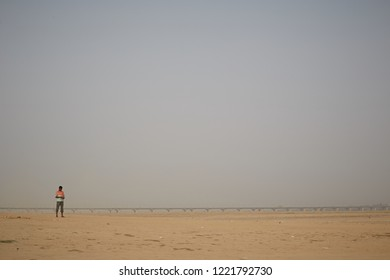 Allahabad, India, November 2015. A man on the sandbank formed by the Yamuna River at its junction with the Ganges, with the bridge at the bottom.