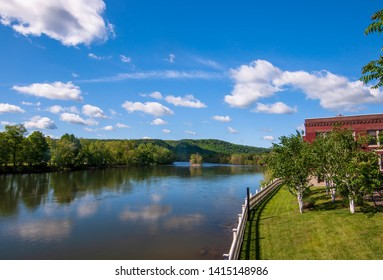 The Allegheny River in Warren, Pennsylvania, USA in springtime under bright blue skies with white clouds