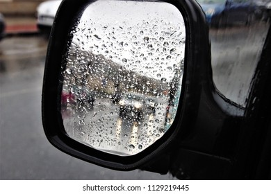 allegory of bad weather, rearview mirror photography of a car with wet glass with raindrops, impressionistic effect,