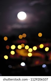 allegory of myopia, Defocused photograph of the moon rising over a village at night.