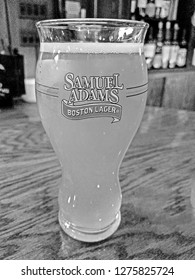 ALLENDALE, NEW JERSEY/USA - FEBRUARY 1, 2018: A Samuel Adams Perfect Pint Glass on the bar at Allendale Bar and Grill. These glasses feature the Samuel Adams logo. Each glass holds 16 fluid ounces.