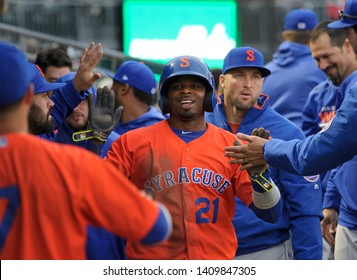 ALLENTOWN, PENNSYLVANIA / USA - APRIL 29, 2019: Syracuse Mets outfielder Rajai Davis is greeted in the dugout as Tim Tebow, right, stands by during a game against the IronPigs at Coca-Cola Park.