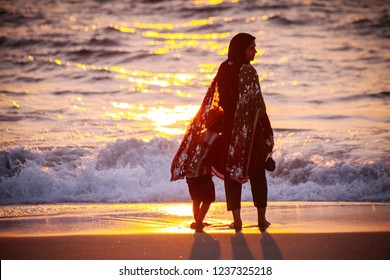 Allepey, INDIA - DECEMBER 17, 2013: Indian woman  in traditional clothes with her child watching sunset  at the Allepey beach