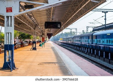 ALLEPPEY, INDIA - FEBRUARY 7: Empty platform under a shed and a train at the Alleppey railway station on February 7, 2016 in Alleppey, India.