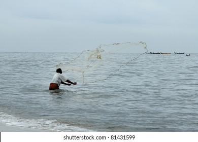 ALLEPPEY, INDIA - JULY 15: A fisherman throws his net in to the Arabian sea on July 15, 2011 in Alleppey, Kerala,India.