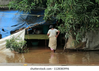 ALLEPPEY, INDIA - JUN 23:Unidentified woman walk in front of her flooded home on June 23,2018 in Alleppey,Kerala, India. Kerala is the most rain affected state in India during the south west monsoon.
