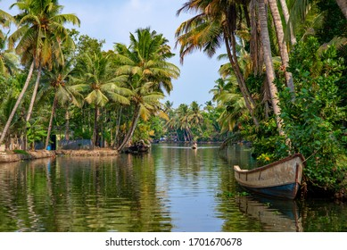 Alleppey, Kerala, India - March 30, 2018: Backwaters canal with palm trees. Taken in the morning with one small boat coming towards the camera from afar.