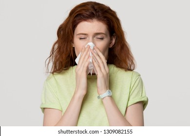 Allergic sick red-haired woman blowing runny nose in tissue got allergy flu, ill redhead lady sneezing holding handkerchief isolated on white grey blank studio background, hay fever rhinitis concept