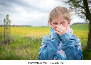 Allergy attack, girl blowing her nose suffering from pollen allergy outdoor in nature