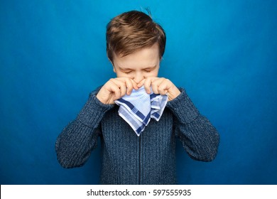 Allergy Boy Child with runny nose holding a handkerchief