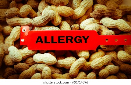 Allergy bracelet over top a pile of peanuts