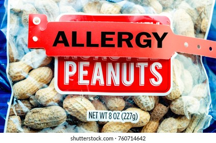 Allergy bracelet over top a pile of peanuts in a bag