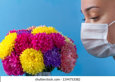 Allergy concept. Allergy to flowers bloom and pollen. A young woman in a medical mask and flowers on a blue background. Allergens, allergic reaction
