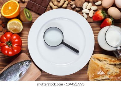 Allergy food concept. Food and empty plate with magnifier on wooden table.