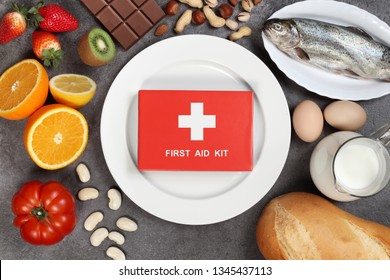 Allergy food concept. Foods, fruits, vegetables, empty plate and first aid kit on grey background