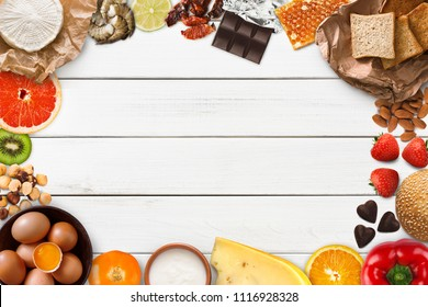 Allergy food concept. Set of allergic products as nuts, cheese, honey, citrus fruits, eggs, chocolate, kiwi, strawberry and seafood on wooden boards, isolated on white wood, top view, copy space