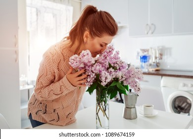Allergy free. Happy woman smelling lilac in modern kitchen. Seasonal allergy concept.