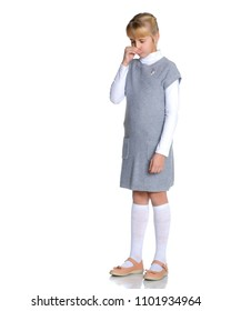 Allergy. Little girl blowing nose in a room on a white background - sneezing girl. The concept of health, ecology. Isolated.