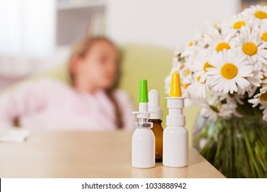 Allergy season concept with blurry person resting in background and medication bottles in the foreground