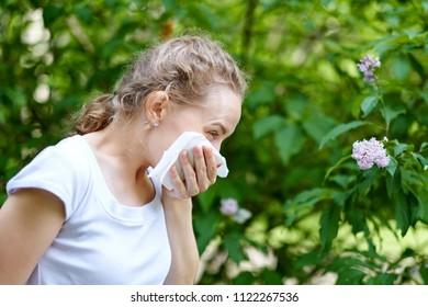 Allergy. Woman blowing her nose when standing close to flowers in a park. Woman with infection sneezing