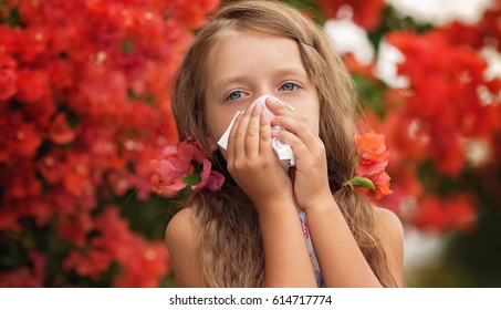 Allergy.Little girl is blowing her nose near spring tree in bloom. Closeup portrait.