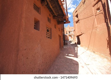 An alley between the reddish wall of stone houses in Abyaneh Village which is the oldest Iranian traditional village renown for it's reddish hue buildings Isfahan Province.
