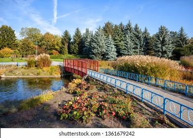Alley in the garden with footbridge on a canal in Edwarda Szymanskiego park in Warsaw, Poland