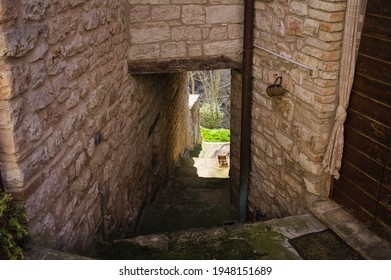 An alley of a medieval village with a tunnel under stone buildings (Marche, Italy, Europe)