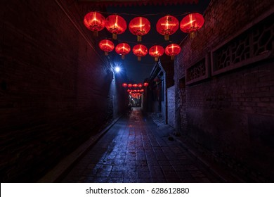 An alley, at night, illuminated by hanging red Chinese lanterns