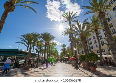 Alley of palm trees is the main tourist street Alicante, Spain, alongside the mediterranean sea. Small market, people are selling hand made souvenirs on street. Beautiful sunny summer evening