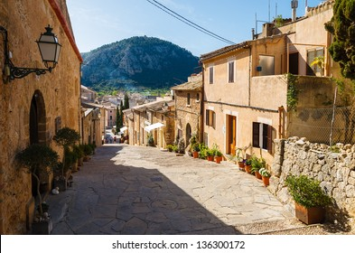 Alley street with traditional house buildings, Pollenca town, Majorca island, Spain