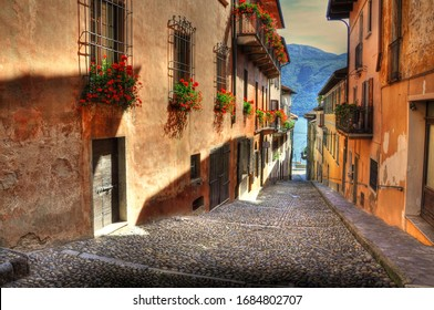 An alley surrounded by buildings decorated with flowers surrounded by a lake in Cannobio in Italy