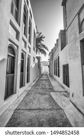 An alleyway in a heritage area of restored traditional arabian houses with shuttered windows and white plasterwork.