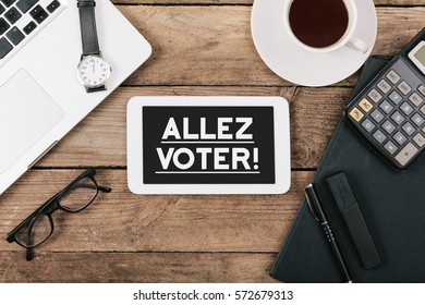 Allez Voter (Go Vote in French) text, office desk with electronic devices, computer and paper, wood table from above, concept image for blog title or header image.