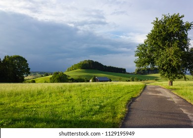 allgau south bavarian landscape with sky clouds and sun beams with green grass and trees