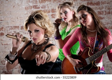 All-girl punk rock band performs in front of a brick background