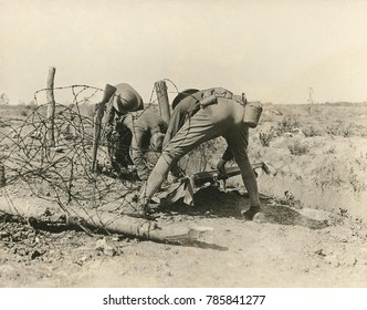 Allied soldiers extricate a casualty entangled in barbed wire, during World War I, 1918. The rifle bayonet stuck into the ground was part memorial, and part battlefield signal to recover a dead body.