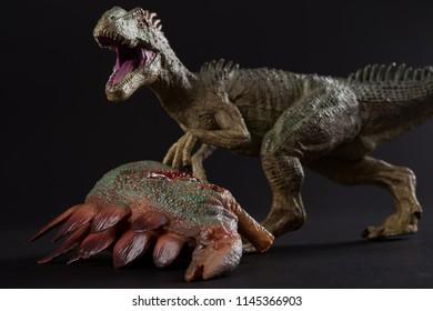 allosaurus with a stegosaurus body nearby on dark background close up
