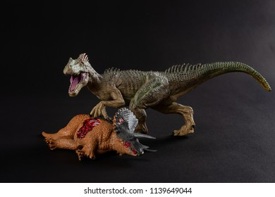 allosaurus with a triceratops body nearby on dark background