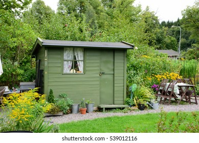 Allotment garden. A green wooden shed with green door and window. Table and chairs.
