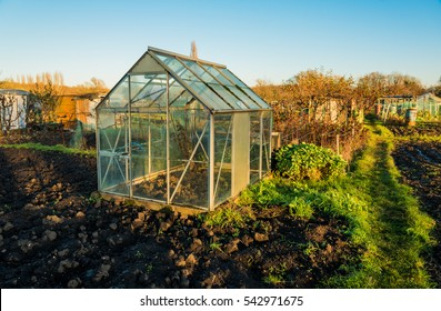 Allotment vegetable gardens with glass greenhouse. Plot with plowed soil ready for sustainable living.