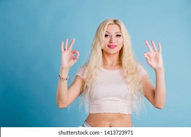 All's right People, body language and emotions concept. Cheerful happy young female with satisfied expression, showing ok sign with both hands, dressed in casual pale pink tee shirt.